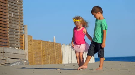 сестры : Beautiful little boy and girl play on the beach holding hands