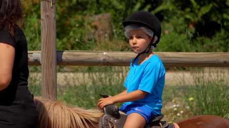верхом : Little boy in blue t-shirt rides a pony and play up