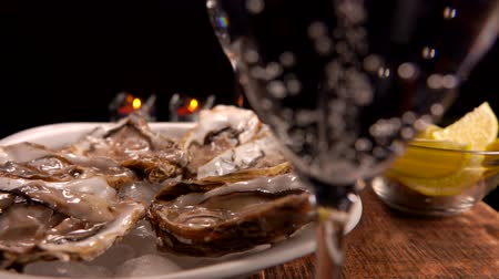 Нормандия : Champagne is poured into a glass on the background of a served table with fresh oysters on ice and candles