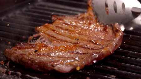 biber tanesi : Cook turns steak with a metal tongs on the grill grate over an open fire