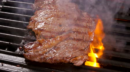 borjúhús : Smoke rises above the steak on a hot grill Spatula presses the steak on the hot surface on the grill with over an open fire. Panoramic camera movement. Stock mozgókép