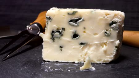 rokfor : Knife cuts and lifts a piece of blue-mold cheese on a black stone board. Panoramic camera movement, close up