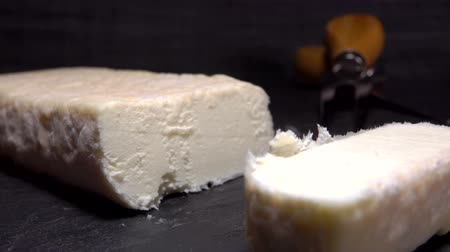 moldy : Knife cuts a piece of soft goat cheese on a black stone board. Panoramic camera movement, close up