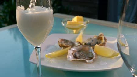 oysters : Champagne is poured into a glass on the background of a plate with oysters on ice.