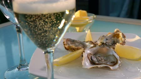 bivalve : Bubbles of champagne rise up in a glass against the background of a plate of oysters on ice and bowls of lemon