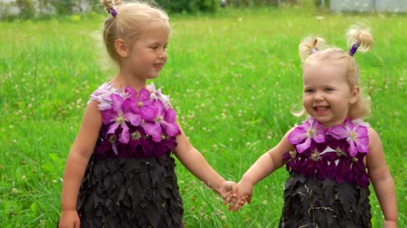 acreditar : Sisters hold hands, smile and dance. Girls wear unusual dresses made of leaves and flowers