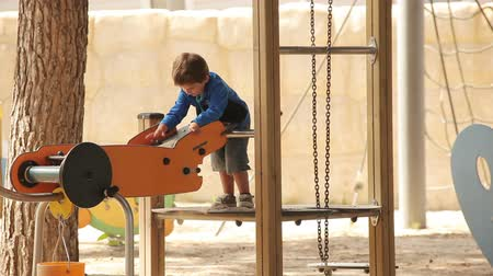 wozek : Little concentrated boy plays educational games with sand at the playground