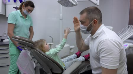 ortodonta : Blond girl gives dentist a high five after checking her teeth. Dental clinic Wideo