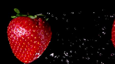 восхитительный : Two juicy tasty large red strawberries collide each other with splashes of water on a black background