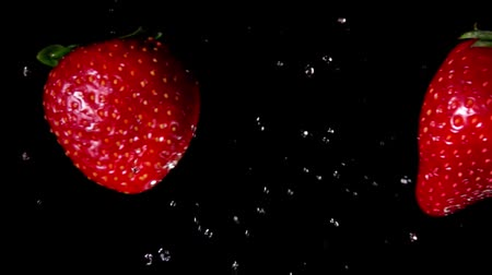 frutoso : Two juicy tasty large red strawberries collide with splashes of water and rotate on a black background Vídeos