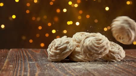 домовой : Meringue cookies fall on a wooden surface on a background of Christmas lights