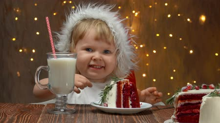 клюква : Girl in red Santa Claus Hat eating red velvet cake with cranberries and drinking milk on the background of christmas lights Стоковые видеозаписи