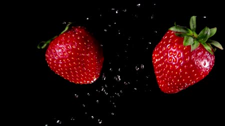 bűbájos : Two delicious red strawberries collide each other with a water splash and rotate on a black background