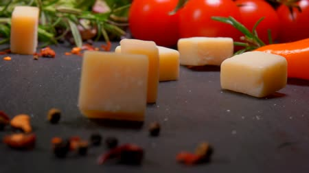 пармезан : Hard cheese cubes fall on a black surface with spices and tomatoes