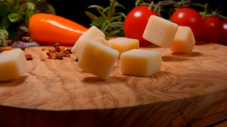 parmigiano : Hard cheese cubes fall on a wooden board on a background of spices and tomatoes