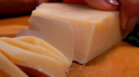 parmigiano : Parmesan cheese cutting with a knife into thin slices on a wooden board