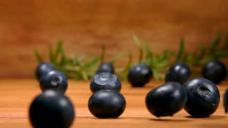 césar : Large blueberries falls and rolls on the wooden table