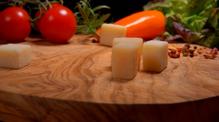 пармезан : Hard cheese cubes fall on a wooden board on a background of spices and tomatoes