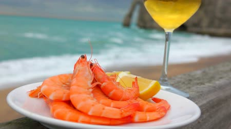 normandie : Delicious shrimps with lemon and white wine on the background of the ocean coast on a cloudy day in Etretat, France Stock Footage