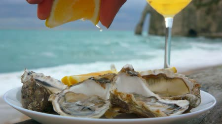 shellfish dishes : Lemon squeezed onto fresh oysters on the background of the ocean coast on a cloudy day in Etretat, France
