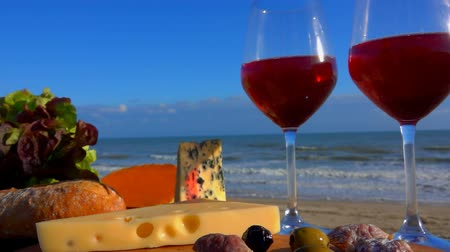 lemoniada : Romantic picnic by the sea with red wine, cheese, bread, lettuce and olives