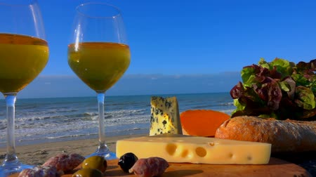 olivy : Romantic picnic by the sea with white wine, cheese, bread, lettuce and olives