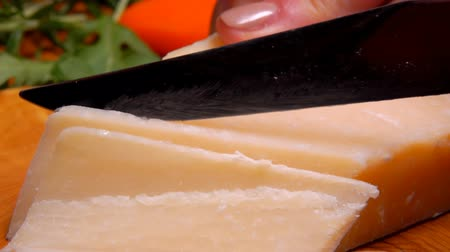 parmigiano : Parmesan cheese is cut into thin slices on a background of green arugula Stock Footage