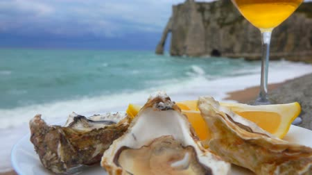 osztriga : Close-up of a plate full of fresh oysters and a glass of white wine against the ocean on a cloudy day in Etretat, France