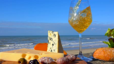 baharatlı alman sosisi : White wine is poured into a glass next to cheese, olives and bread on a background of the sea coast on a clear day Stok Video