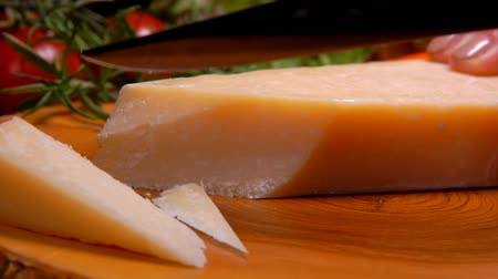 parmigiano : Hard Parmesan Cheese is cut with a knife into thin slices on a wooden board on a background of greennnery and tomatoes Stock Footage