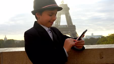 フランス : Beautiful teenager boy in a hat reads messages on the phone, writes SMS and smiles on the background of the Eiffel tower, Paris, France