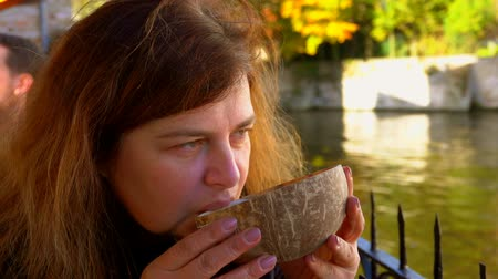 sede : Woman tourist drinks coconut beer from the half of coconut shell in a bar by the river, Belgium