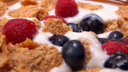 flocos de milho : Spoon takes yogurt with berries from a glass bowl with raspberries, blueberries and cornflakes. Healthy breakfast