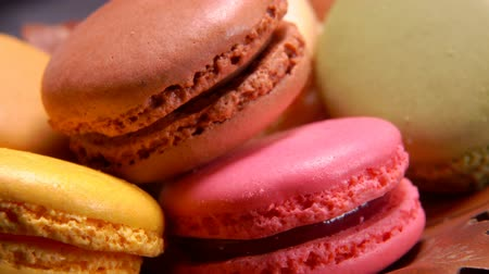 baunilha : Close-up of multi-colored French macaroons lie on a brown plate Stock Footage