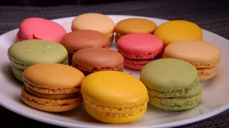candy : Multi-colored French macaroons lie on a white plate. Many hands take macaroons from a plate