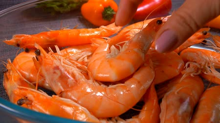 istiridye : Hand takes delicious large unpeeled shrimp from a glass bowl Stok Video