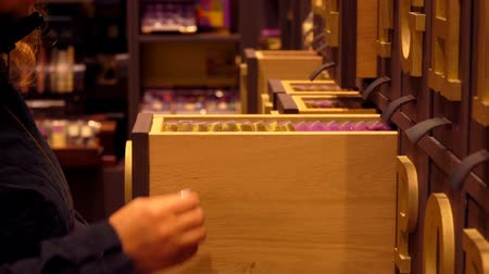 bruges : Woman opens drawers with beautifully packed boxes of chocolate in a confectionary store, Belgium Stock Footage