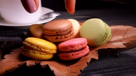 acıbadem kurabiyesi : Multi-colored French macaroons lie in a plate in the form of a leaf on a background of a cup with coffee. Hand take macaroon from a plate