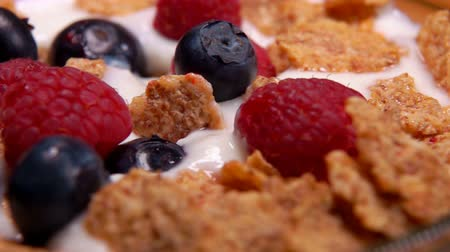 antioksidan : Healthy breakfast: raspberries and blueberries fall on cereal yogurt Stok Video