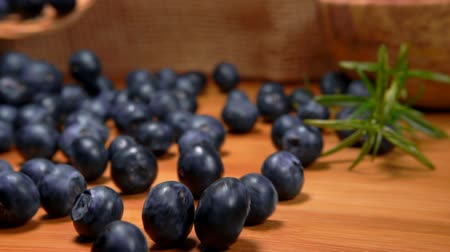 césar : Large delicious ripe blueberries spill out of the basket on a wooden table surface