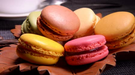 миндальное печенье : Tasty sweet french macaroons lie on a plate on a background of a cup with coffee Стоковые видеозаписи