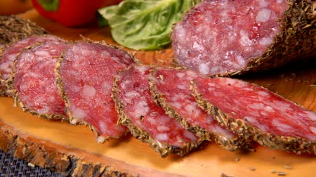 вылеченный : Slices of tasty dried sausage in herbs is taken with fork from a wooden surface
