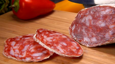 вылеченный : Appetizing panorama of dry sausage in white skin cut with a knife on a wooden board