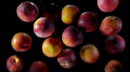 nectarina : Juicy tasty peaches fly up and bounce on a black background