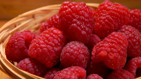 wiklina : Hand takes a big juicy appetizing raspberries out of wicker basket