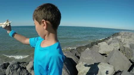 sand paper : Boy plays with a model airplane on the seashore against a clear clear sky. Boy mimics the sounds of flight