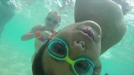 Boy in swimming goggles dives and swims underwater. Camera rotating after boy swirling under water
