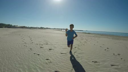 Boy runs along the beach with an airplane model in his hands towards the camera