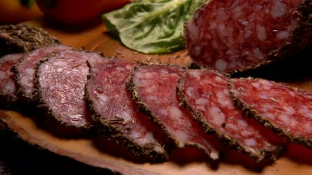 smoked : Slices of dried sausage in herbs lying on a wooden surface and taken with fork against the greenery Stock Footage