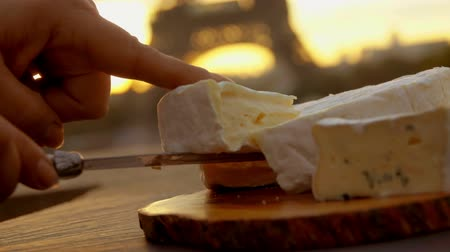 пармезан : Hand takes a piece of brie cheese from a wooden board on the background of the Eiffel Tower, Paris, France